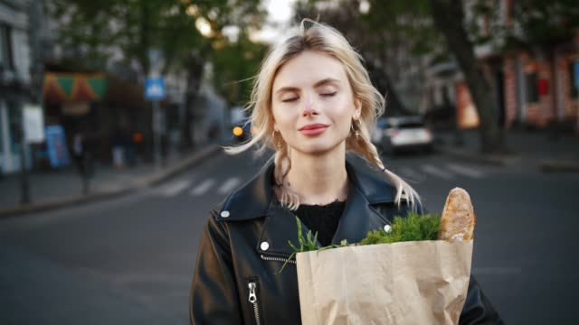 portrait of young cheerful women holding paper bag of groceries from supermarket outdoors in old city center, slow motion - francuska kuchnia filmów i materiałów b-roll