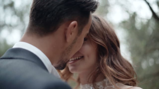 portrait of young couple in love full of passion and emotions, man on dating kissing his pretty girlfriend and smiling, love and tenderness in air. romantic dating of man and woman, affection from the first sight - young couple wedding friends video stock e b–roll