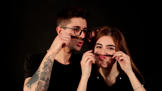 portrait of young couple making mustache from hair - brunette woman eyeglasses kiss man video stock e b–roll