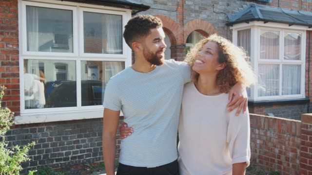 portrait of young couple standing outside new home in urban street - couple portrait caucasian video stock e b–roll