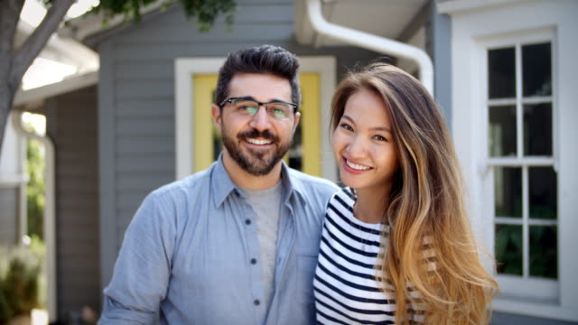 portrait of young couple standing outside new home - new home stock videos & royalty-free footage