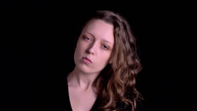 portrait of young curly-haired girl posing seriously and flirtingly into camera on black background. - occhiata laterale video stock e b–roll