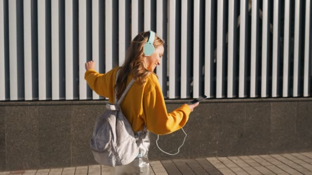 Portrait of young cute attractive young girl in urban background listening to music with headphones. Woman wearing yellow blouse and silver skirt