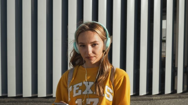 vídeos de stock e filmes b-roll de portrait of young cute attractive young girl in urban background listening to music with headphones. woman wearing yellow blouse and silver skirt - cool