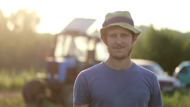 vídeos de stock e filmes b-roll de portrait of young farmer in hat standing at field of organic farm and smiling - farmer