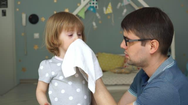 Porträt des jungen Vaters mit Gläsern wippen laufende Nase und Tränen der kleinen niedlichen Tochter mit einer Serviette. – Video