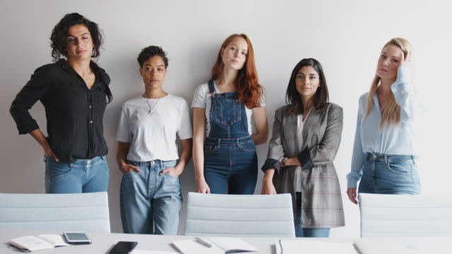Portrait Of Young Female Business Team Standing Against Wall In Modern Office