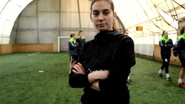 porträtt av unga kvinnliga fotbollspelare, tittar på kameran med armarna korsade - femininitet bildbanksvideor och videomaterial från bakom kulisserna