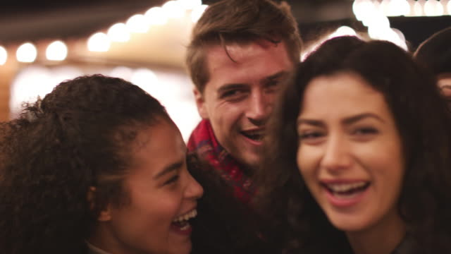 Portrait Of Young Friends Enjoying Christmas Market At Night video