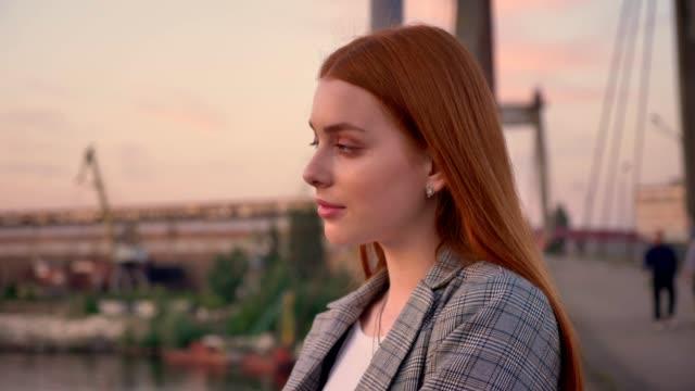 stockvideo's en b-roll-footage met portret van jonge gember vrouw staande op de brug, op zoek weg en vervolgens in de camera, glimlachen, zonsondergang - men blazer