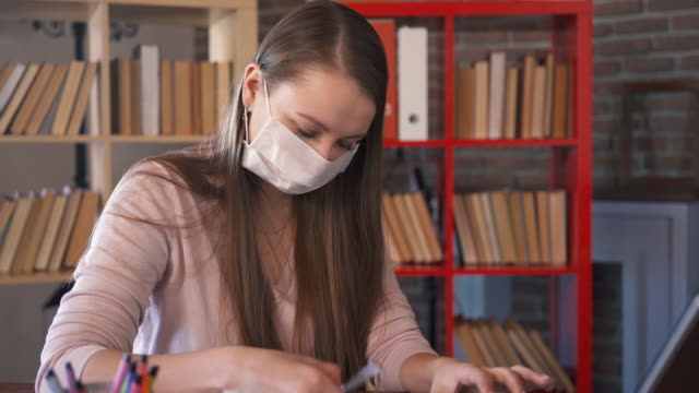 portrait of young girl freelancer wearing protective mask in home office. woman in medical mask working on workplace. coronavirus epidemic, 2019-ncov covid-19 pandemic. quarantine and self isolation. - studente universitario video stock e b–roll