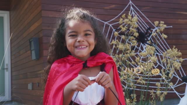 portrait of young girl wearing fancy dress outside house collecting candy for trick or treat - widok od przodu filmów i materiałów b-roll