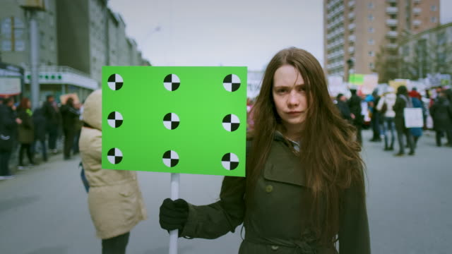 portrait of young girl with an empty banner for your text looking at the camera. - traccia video stock e b–roll