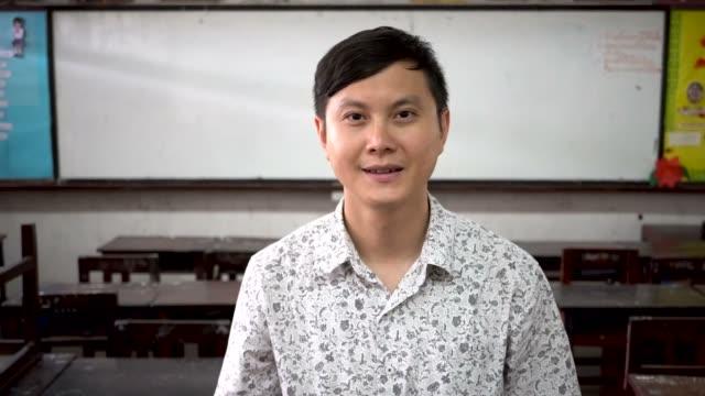 Retrato de jovem bonito asiático masculino professor sorrindo dentro da sala de aula - vídeo