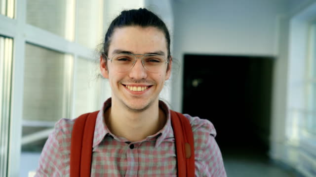 Portrait of young handsome attractive male student of caucasian ethnicity standing in wide white hallway indoors looking at camera and smiling positively video