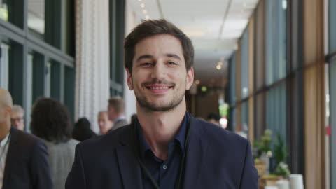 vidéos et rushes de verticale de jeune homme d'affaires beau au séminaire - portrait