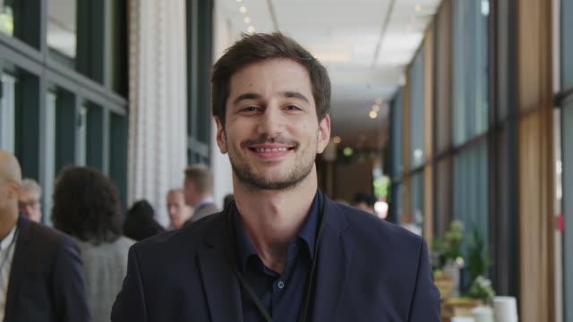年輕英俊商人在研討會上的肖像 - 微笑 個影片檔及 b 捲影像