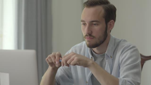 porträtt av ung stilig man bryta penna med ilska sitter framför sin dator på kontoret. - blyertspenna bildbanksvideor och videomaterial från bakom kulisserna