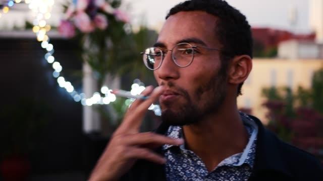ritratto di giovane bel uomo di razza mista con occhiali che hanno una sigaretta di notte - sigaretta video stock e b–roll