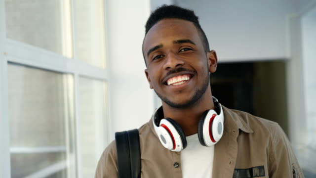 Portrait of young handsome student of african-american ethnicity standing in wide white spacious corridor of college with hedphones looking at camera and smiling video