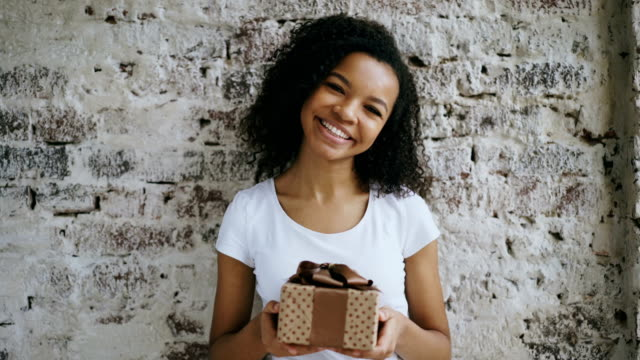 Portrait of Young happy african girl holding gift box and smiling into camera video