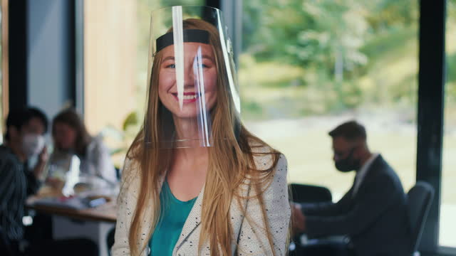 Portrait of young happy Caucasian business woman wearing transparent face shield protection at workplace slow motion.