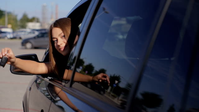 Portrait of young happy female taking driving lessons in car video
