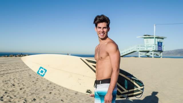 porträt des jungen hispanischen surfer am strand - nackter oberkörper stock-videos und b-roll-filmmaterial