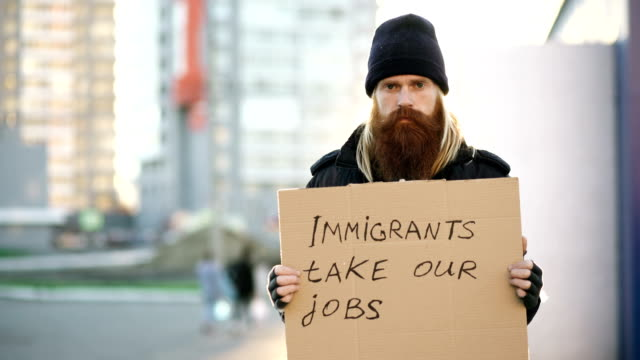 Portrait of young homeless man with cardboard looking at camera and very upset because of immigrants crisis in Europe video