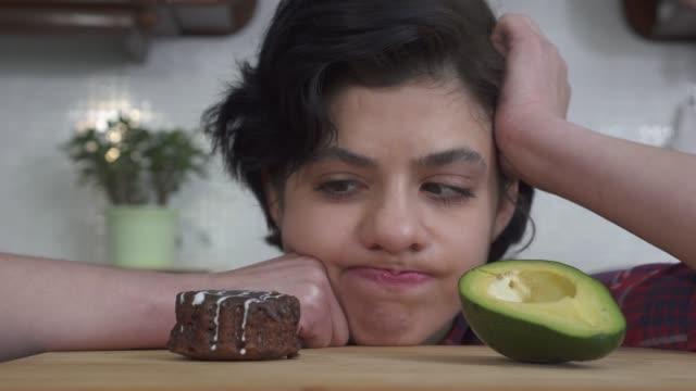 porträtt av ung hungrig flicka att välja mellan färsk avokado och välsmakande brownie tårta och efter att ha ätit tårta. - brownie bildbanksvideor och videomaterial från bakom kulisserna