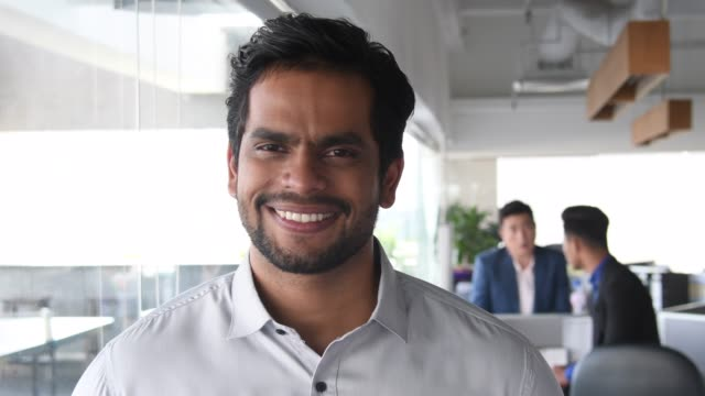 portrait of young indian man in modern office smiling - portrait stock videos & royalty-free footage