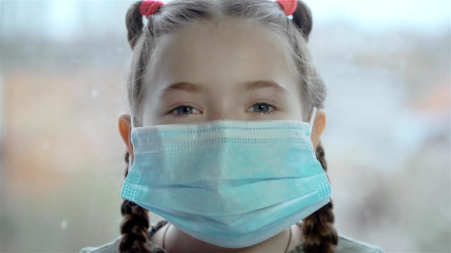 Portrait of young little girl wearing protective mask on window background for saving health and safety life
