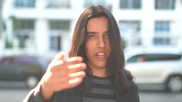 vídeos de stock e filmes b-roll de portrait of young man beckoning - cabelo comprido