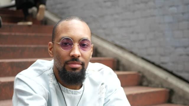 ritratto di giovane seduto fuori - barba peluria del viso video stock e b–roll