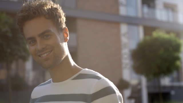 vidéos et rushes de portrait de jeune homme souriant à une caméra, à l'extérieur. - charmeur