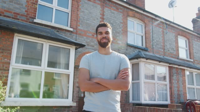 porträtt av ung man som stod utanför nya hem i urban street - framifrån bildbanksvideor och videomaterial från bakom kulisserna