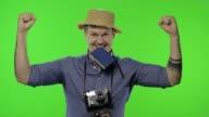 istock Portrait of young man tourist photographer celebrates and dances. Chroma key 1222114517