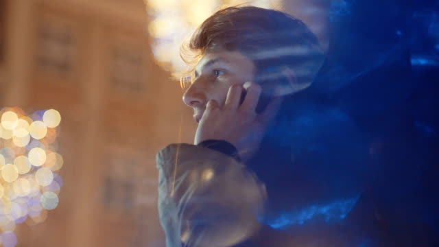 Portrait of young man using his mobile phone at night. video