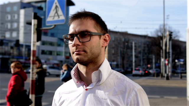 portrait of young man wearing eye glasses walking in the city streets. - young singles stock videos & royalty-free footage