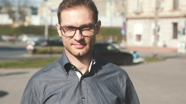 Portrait of young man wearing eye glasses walking in the city streets. Handsome guy walking in the city street, slow motion. Business, people and happiness concept. young singles stock videos & royalty-free footage