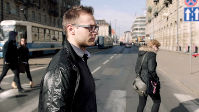 porträt eines jungen mannes tragen brillen zu fuß in die stadt. - überweg warnschild stock-videos und b-roll-filmmaterial