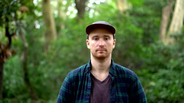 vídeos de stock e filmes b-roll de portrait of young man with serious facial expression looking in camera - aproximar imagem