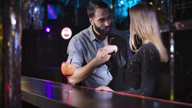 ritratto di giovane mediorientale e donna caucasica che si incontrano nel night club. coppia allegra in piedi accanto al bancone del bar con cocktail e chiacchiere. quartier generale cinema 4k prores. - flirtare video stock e b–roll