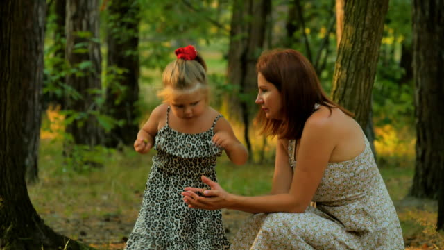Portrait of young mother and daughter collects cones and acorns in the forest video