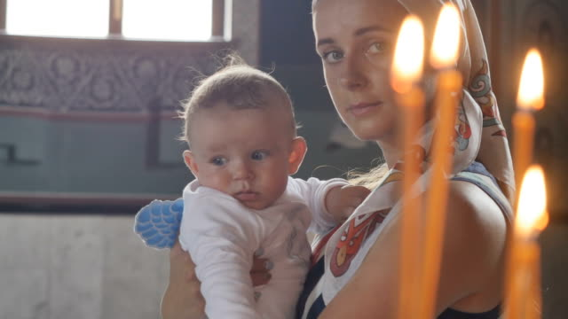 Portrait of young mother with little son in front of candles in church video