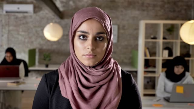 portrait of young muslim women in hijab looking in camera, serious and concerned, three pretty womens working on laptop in modern office - sciarpa video stock e b–roll