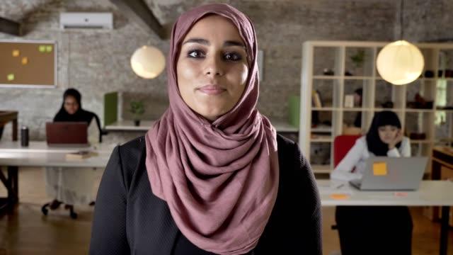 porträtt av unga muslimska kvinnor i hijab inne i kameran, två womens sitter och skriver på laptop i office på bakgrunden - hijab bildbanksvideor och videomaterial från bakom kulisserna