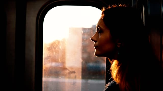 Portrait of young pensive woman taking subway in Chicago, America on sunset. Sad female inside of moving train