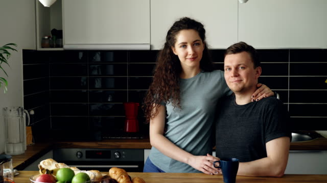 portrait of young positive smiling caucasian couple in kitchen, beautiful woman is standing near handsome man, she is hugging him, they are looking into camera - couple portrait caucasian video stock e b–roll