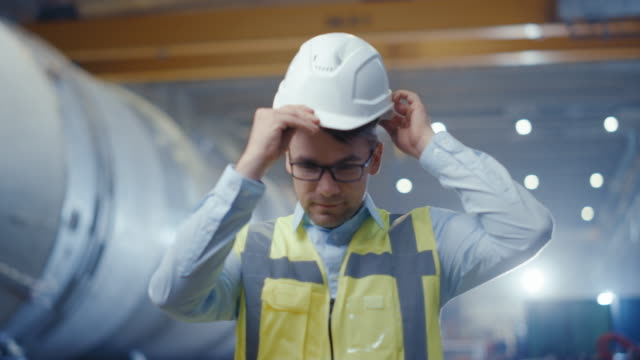Portrait of Young Professional Heavy Industry Engineer / Worker Wearing Safety Vest, Putting on Hardhat. In the Background Unfocused Large Industrial Factory where Welding Sparks Flying. Slow Motion